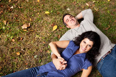 Daydream Park Couple. A happy couple daydreaming in a park on grass - sharp focus on woman Royalty Free Stock Photo