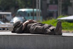 Daydreamer. Chinese man asleep in the town square of Urumqi, Xinjiang China Stock Image