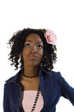 Daydreamer. Gorgeous african-american model in a pink dress, denim jacket and pink camellia in the hair Stock Photo