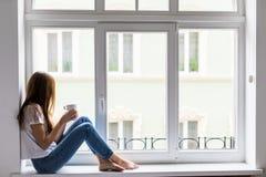 Daydreamer hermoso Mujer joven hermosa que sostiene la taza de café con sonrisa mientras que se sienta en el alféizar en casa imagen de archivo