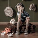 Daydreamer pequeno que senta-se na mala de viagem Imagens de Stock