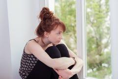 Daydreaming молодой женщины redhead сидя стоковые фото