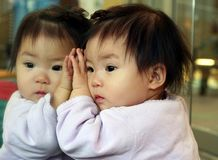 Daydreaming. Baby looking at herself in the mirror and daydreaming stock images