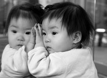 Daydreaming. Baby looking at herself in the mirror and daydreaming stock image