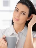 Daydreaming beauty with coffee. Daydreaming beauty posing with coffee mug in hand, smiling Royalty Free Stock Image