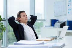 Daydreaming businessman. Businessman daydreaming in the office with hands behind his head Royalty Free Stock Images