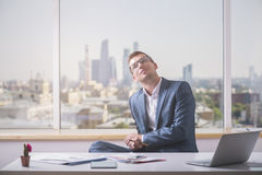 Daydreaming businessman in office. Daydreaming young businessman in suit sitting at office desk with electronic devices and paperwork Royalty Free Stock Photos