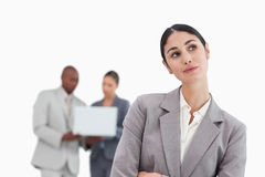 Daydreaming businesswoman with colleagues behind her Stock Images