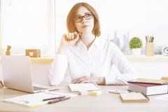 Daydreaming businesswoman in office. Attractive daydreaming businesswoman sitting at office desktop with laptop and other items. Window with city view in the Royalty Free Stock Image