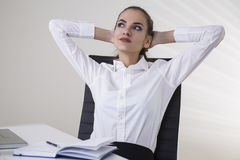 Daydreaming businesswoman in office. Portrait of a relaxed brown haired businesswoman in a white blouse sitting at her table in an office with her hands behind Stock Photos