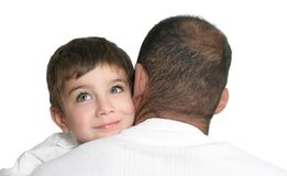 Daydreaming child. In fathers arms, looking up and smiling, space for text Stock Photo