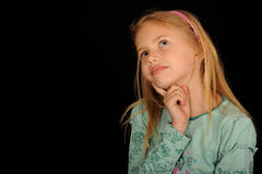 Daydreaming Girl. A portrait of a cute daydreaming girl, on black studio background Stock Image