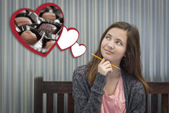 Daydreaming Girl Next To Floating Hearts with Chocolates Royalty Free Stock Image