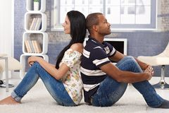 Daydreaming happy couple at home. Happy interracial couple sitting on floor back-to-back, daydreaming, smiling Stock Photos