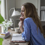 Daydreaming in the home office. Attractive woman sitting in her home office in the morning Royalty Free Stock Photo