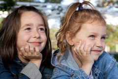 Daydreaming kids. Two pretty little girls daydreaming outdoors Royalty Free Stock Photo