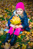 Daydreaming little girl with bouquet of maple leaves in autumn p Royalty Free Stock Photos
