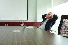 Daydreaming. Middle-aged businessman daydreaming in the office Royalty Free Stock Photo
