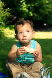 Daydreaming With Sandwich. Toddler sitting on the grass holding sandwich looking up with dreamy look on face Stock Photo