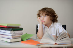 Daydreaming schoolboy sits at a school desk Stock Photography