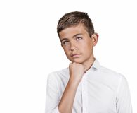 Daydreaming teenager boy, chin on hand, looking up Royalty Free Stock Photos
