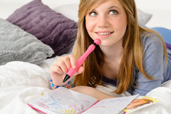 Daydreaming teenager girl writing her journal Stock Images