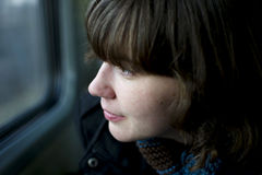 Daydreaming traveler. Young traveler looking outside the train window, daydreaming Stock Images