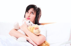 Daydreaming woman in bed with teddy Royalty Free Stock Photo
