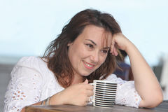 Daydreaming woman with a cup of drink Stock Photo