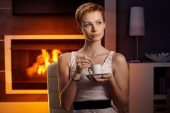 Daydreaming woman drinking coffee at home Stock Photo