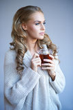 Daydreaming woman drinking tea Stock Images