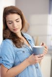 Daydreaming woman drinking tea at home. Young attractive woman drinking tea at home, daydreaming Royalty Free Stock Photography