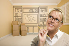 Daydreaming Woman Holding Pencil In Rom with Shelf Drawing on Wa. Daydreaming Woman Holding Pencil In Empty Rom with Built In Shelf Design Drawing on Wall Stock Photo