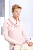 Daydreaming woman standing in pink pullover Royalty Free Stock Photography