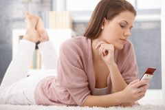 Daydreaming woman using cellphone Royalty Free Stock Photography
