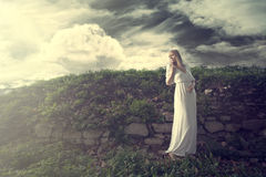 Daydreaming. Young blonde woman in long white dress with twig of flowers in hand stand by old wall overgrown with grass, outdoor shot, full body shot Stock Photo