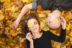 Daydreaming. Young male and female lying down on yellow maple leaves smiling happy having good time eyes closed Stock Photos