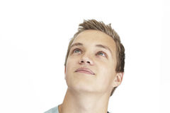 Daydreaming young man. A daydreaming young man on a white background Royalty Free Stock Photo