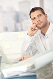 Daydreaming young man sitting at desk. With lots of folders Royalty Free Stock Photography