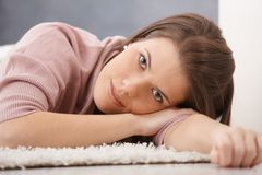 Daydreaming young woman on floor Stock Image