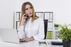 Daydreaming young woman on phone in white office. Dreamy young woman in a white blouse is on her phone while typing with one hand. Concept of daydreaming Royalty Free Stock Photo