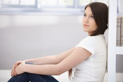 Daydreaming young woman sitting on floor Royalty Free Stock Photos