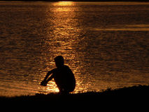 The Daydreams. The Sitting boy on background of the reflection sun on water Stock Photo