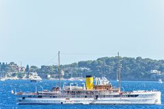 Daylight close-up view to tourists ship cruising on water. Yachts, green trees and buildings on background. Bright blue clear sky. Negative copy space, place Stock Photos
