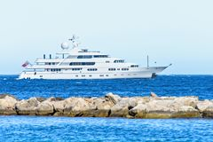 Daylight close-up view to white yacht cruising on water and spli. Tting rocks. Bright blue clear sky. Negative copy space, place for text. Cap d`Ail, france Royalty Free Stock Photos