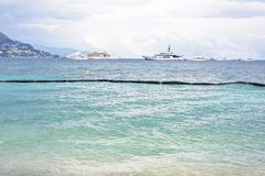 Daylight cloudy day view to beachline with ships cruising on wat Stock Image