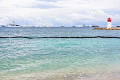 Daylight cloudy day view to beachline with ships cruising on wat Stock Photo