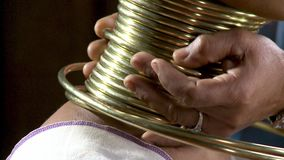 Fitting the neck with layers of gold ring coils
