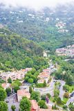 Daylight foggy view to Eze, Cote d`Azur village with medieval ho. Daylight foggy view to Eze, France Cote d`Azur village with medieval houses, roads and green royalty free stock image