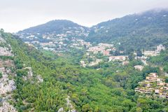 Daylight foggy view to Eze, Cote d`Azur village with medieval ho. Daylight foggy view to Eze, France Cote d`Azur village with medieval houses, roads and green stock photo